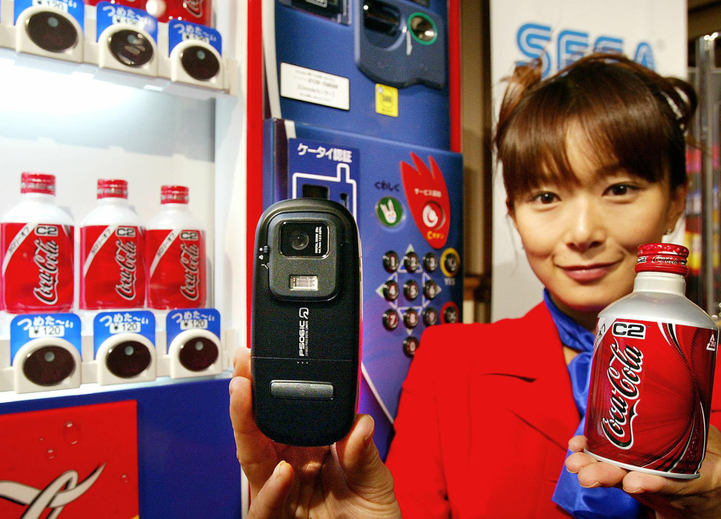 (FILES) This file picture taken on June 16, 2004 shows an employee for Coca-Cola Japan demonstrating how to buy a soft drink from a vending machine with a mobile phone equipped with Sony's NFC technology FeliCa in Tokyo. Felica NFC with mobile phones for the mobile wallet were launched in Japan in 2004, while Apple unveiled the new iPhone 6 on September 9, 2014 with the NFC chip to start the mobile wallet service.   AFP PHOTO / FILES / Yoshikazu TSUNO